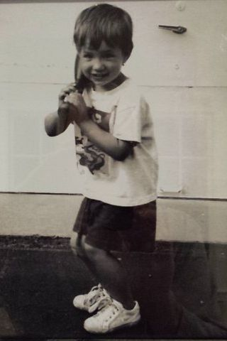 Adam Ravenelle as a toddler, holding the bat he'd use to crush the wiffle balls his parents tossed his way.