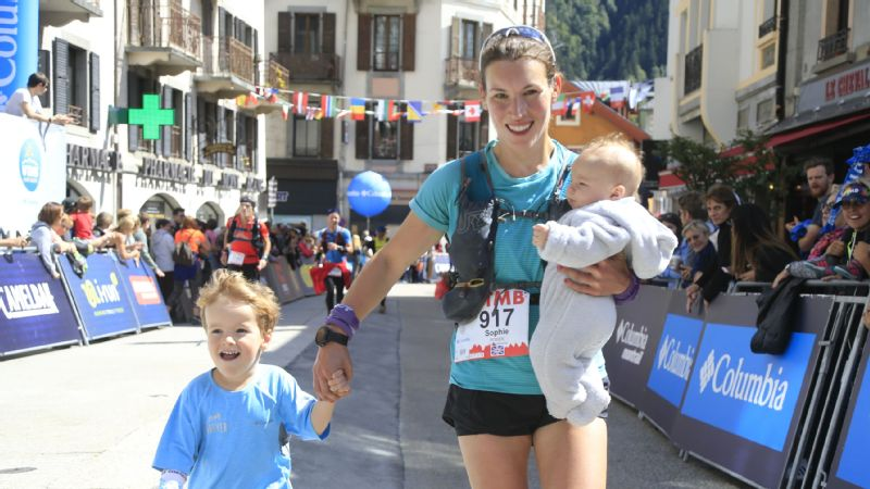 Sophie Power runs across the Ultra-Trail du Mont-Blanc finish line with her infant son, Cormac, and toddler, Donnacha.