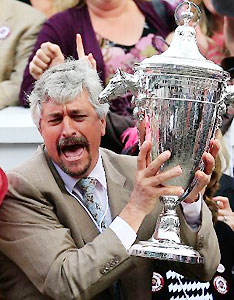 Trainer Steve Asmussen celebrates with the trophy after the 2014 Kentucky Oaks.