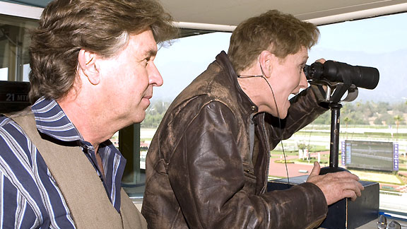 Trevor Denman looks on as late-night host Conan O'Brien fills in for a race at Santa Anita.