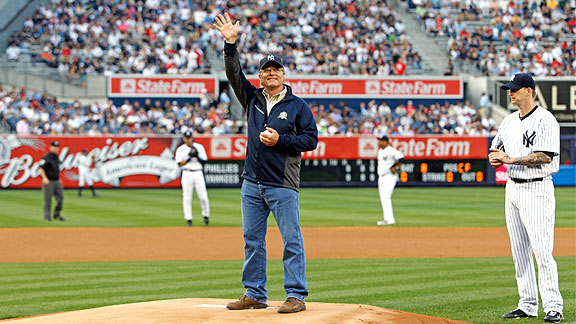 Trainer Bill Mott throws out the first pitch at a New York Yankees baseball game.