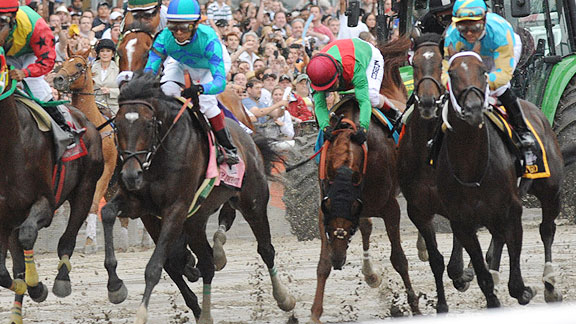 Jockey John Velazquez is almost unseated when Animal Kingdom is bumped leaving the starting gate in Saturday's Belmont Stakes.