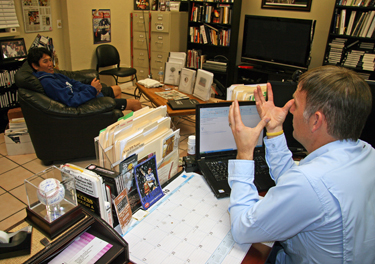 Trevor Moawad, director of Athletic & Personal Development program, keeps an autographed photo of Tak Omori on his desk to remind him of how athletic training extends to the professional bass fishing arena.
