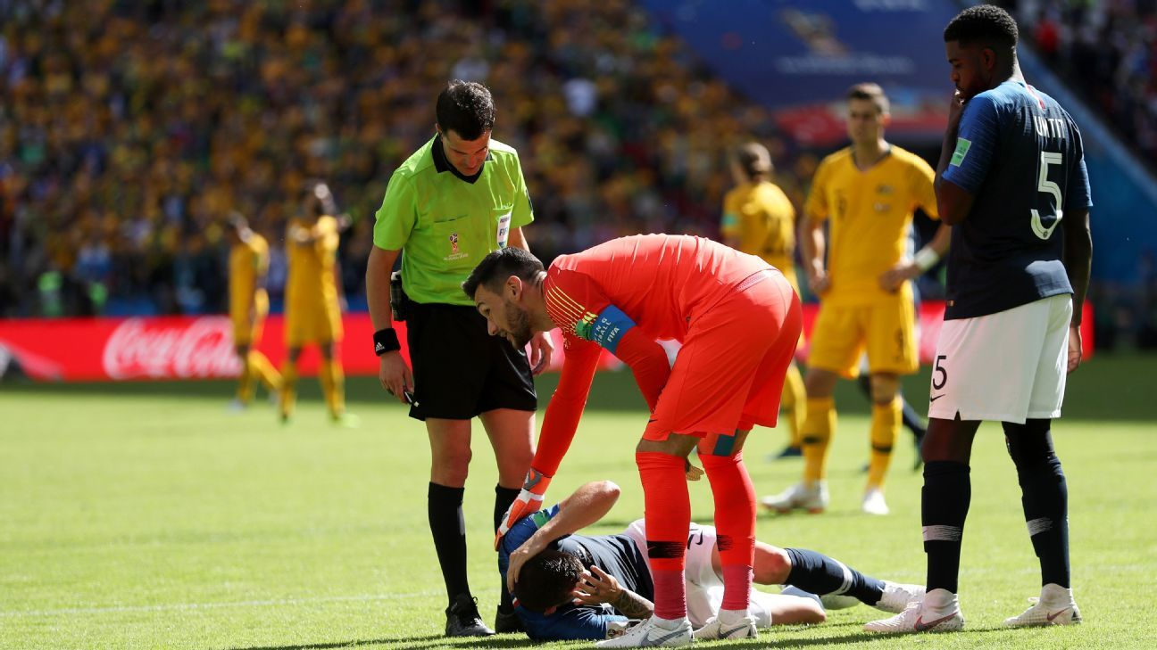 France's Lucas Hernandez is checked on by teammates Hugo Lloris and Samuel Umtiti.