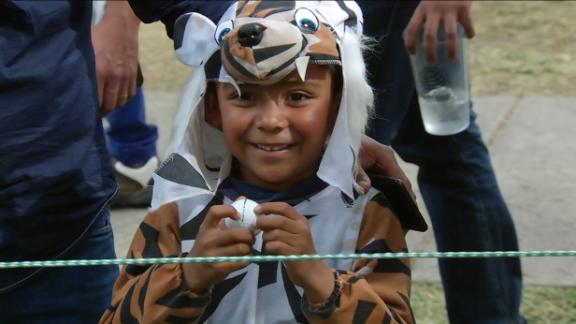 Tiger surprises young fan in tiger costume with ball