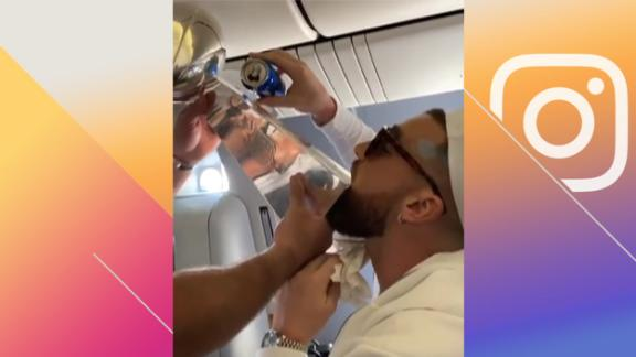 Travis Kelce chugs a beer from the Lombardi Trophy