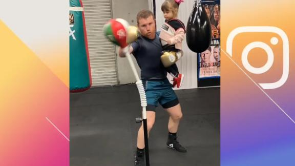 Canelo trains while holding his daughter