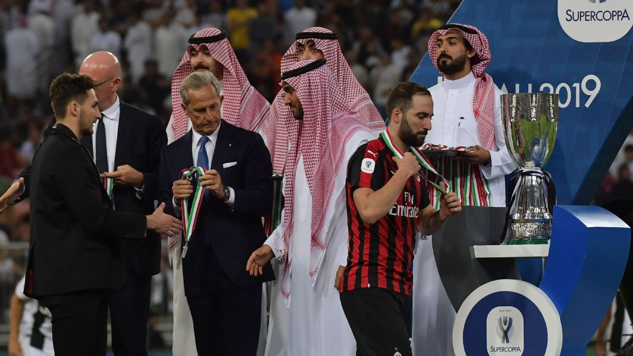 Gonzalo Higuain accepts his runner-up medal after AC Milan lost to Juventus in the Italian Supercoppa.
