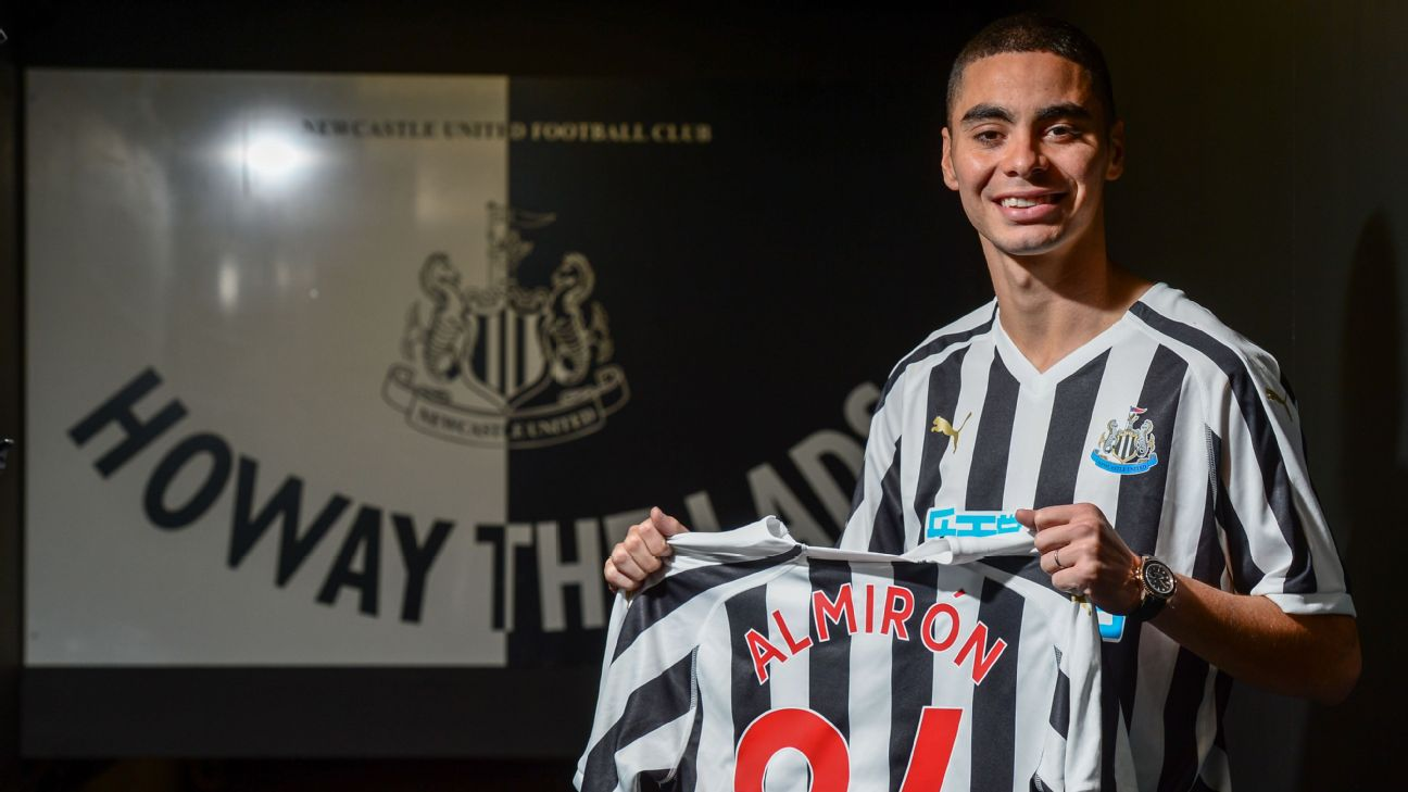 Miguel Almiron holds up a jersey for his new club after signing for Newcastle United.