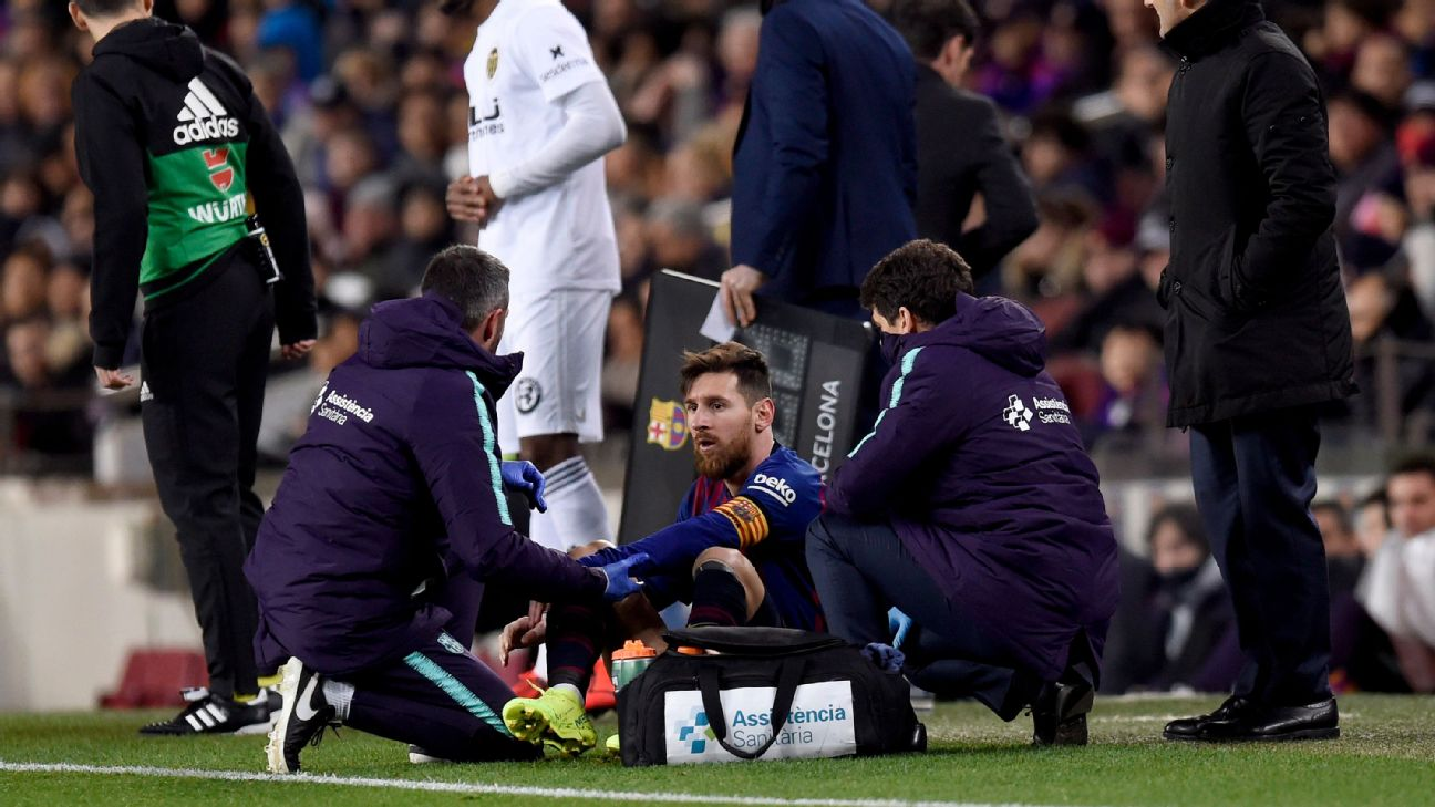 Barcelona team medics tend to Lionel Messi on the sidelines during their match with Valencia.