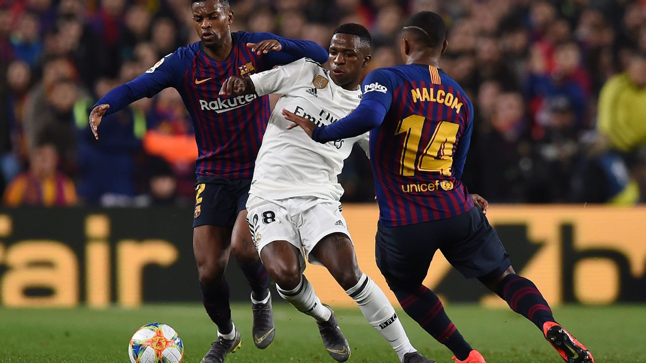 Real Madrid's Vinicius Jr., centre, battles countryman Malcom of Barcelona for the ball in the Copa del Rey.