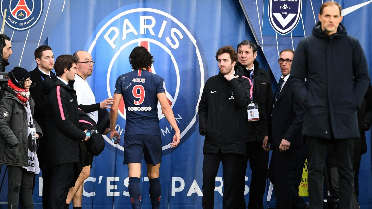 Edinson Cavani (C) leaves the football pitch after an injury next to Paris Saint-Germain's German head coach Thomas Tuchel