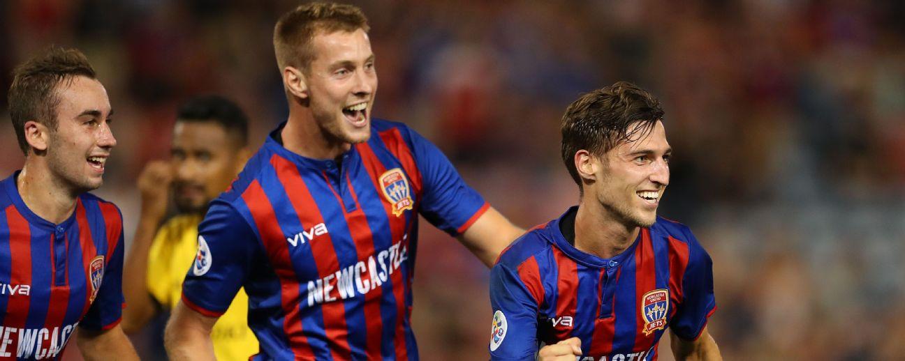 Matthew Ridenton of the Newcastle Jets celebrates a goal with team mates