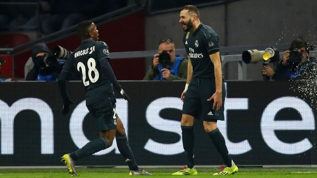 Vinicius Junior, left, celebrates with Real Madrid teammate Karim Benzema after scoring a goal.