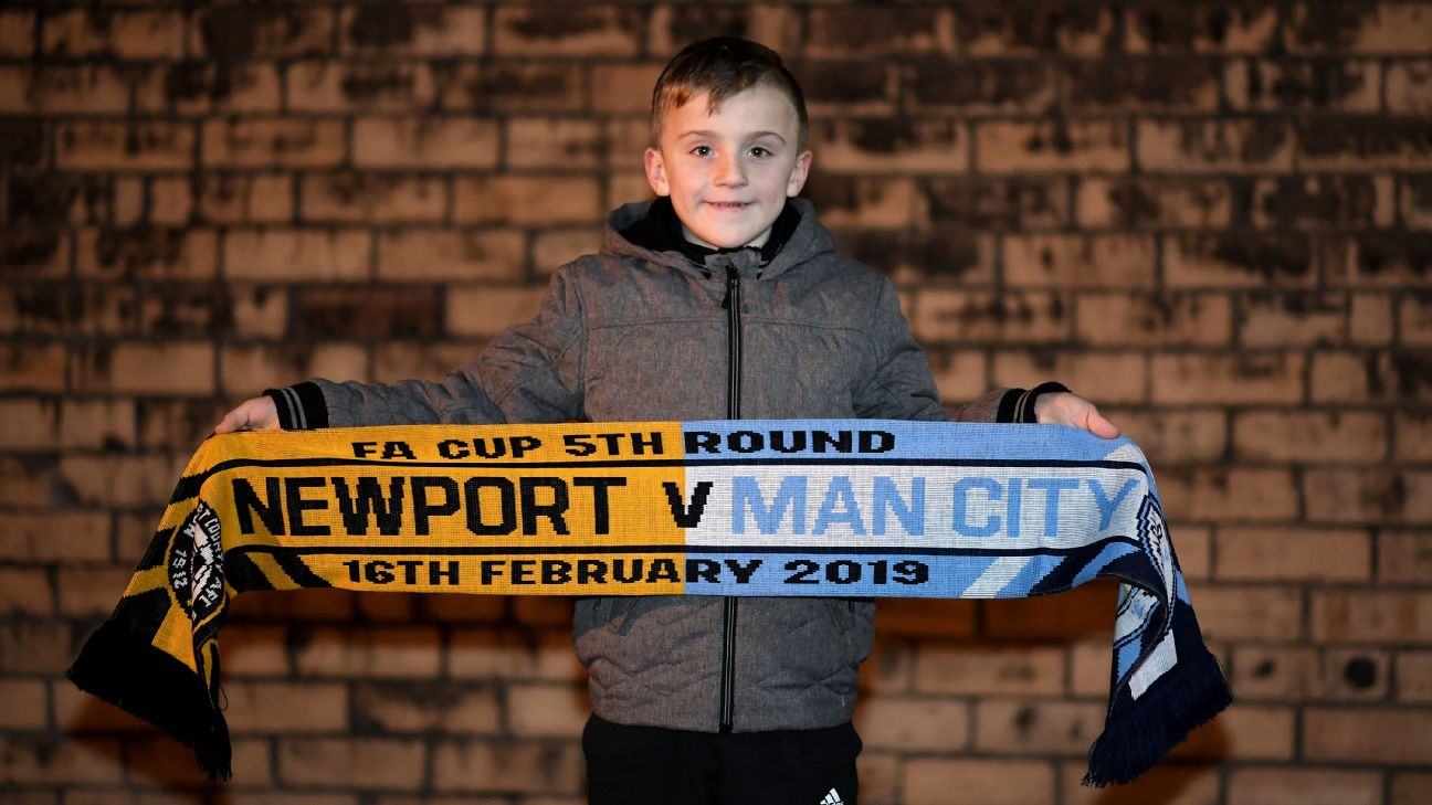 A fan poses for a photo with a Newport County vs. Manchester City scarf.