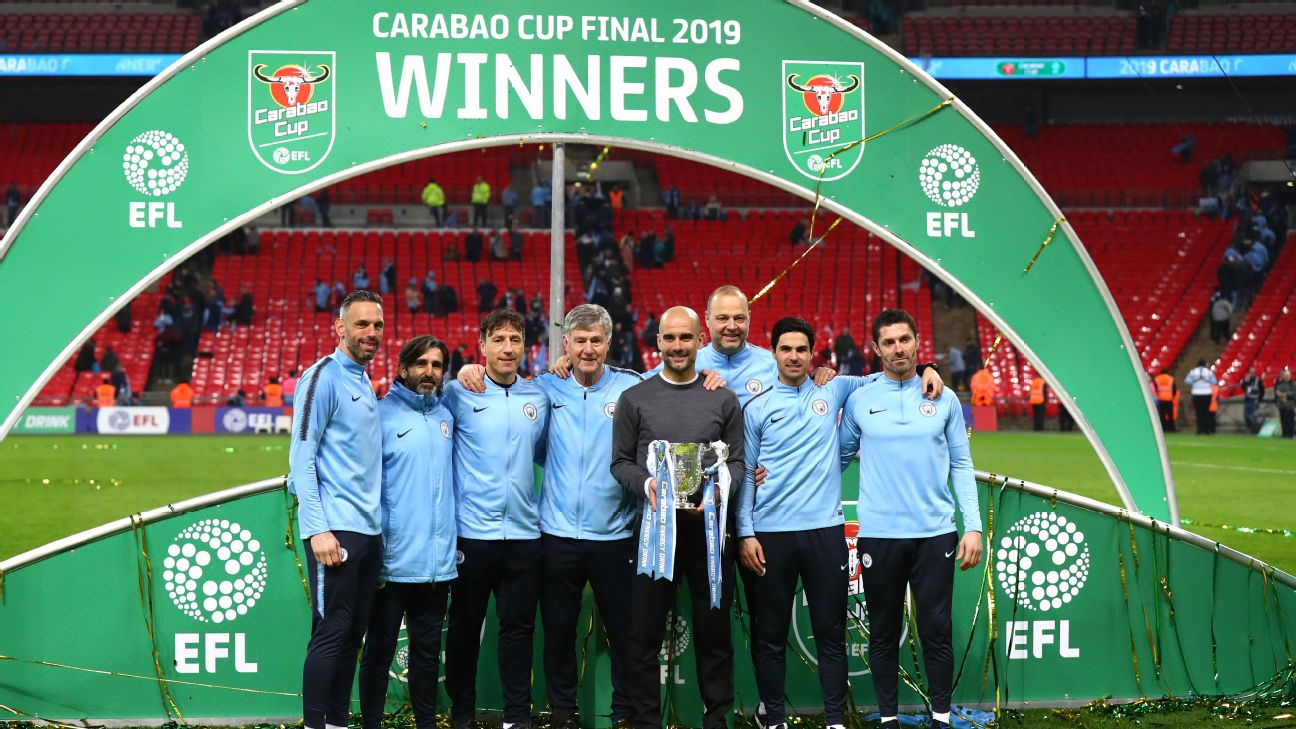 Pep Guardiola and his Manchester City staff pose with the Carabao Cup trophy at Wembley