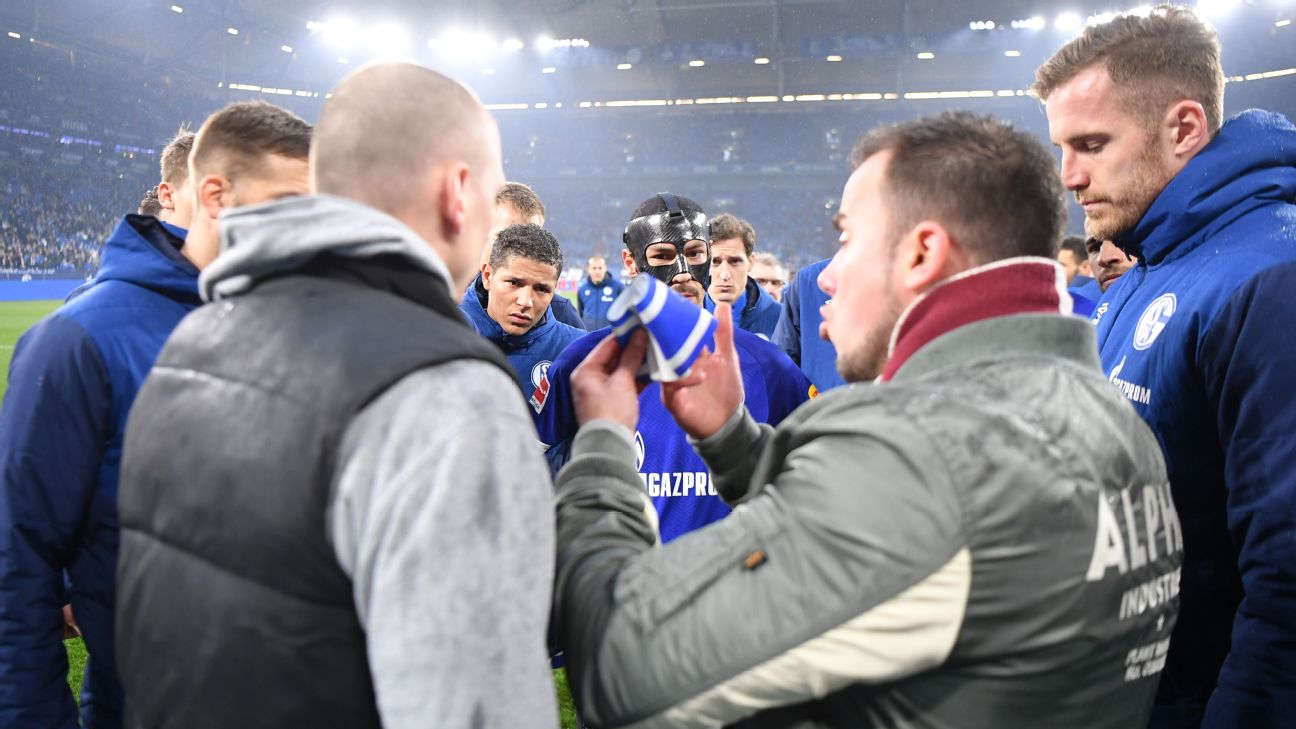 Schalke captain Benjamin Stambouli gives an armband to fans who made their way onto the pitch.