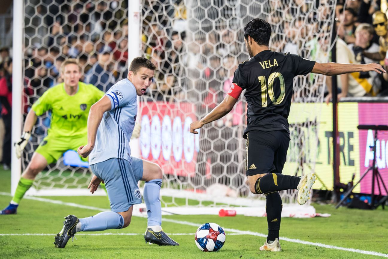 Carlos Vela, left, dribbles the ball toward goal in LAFC's match against Sporting KC.