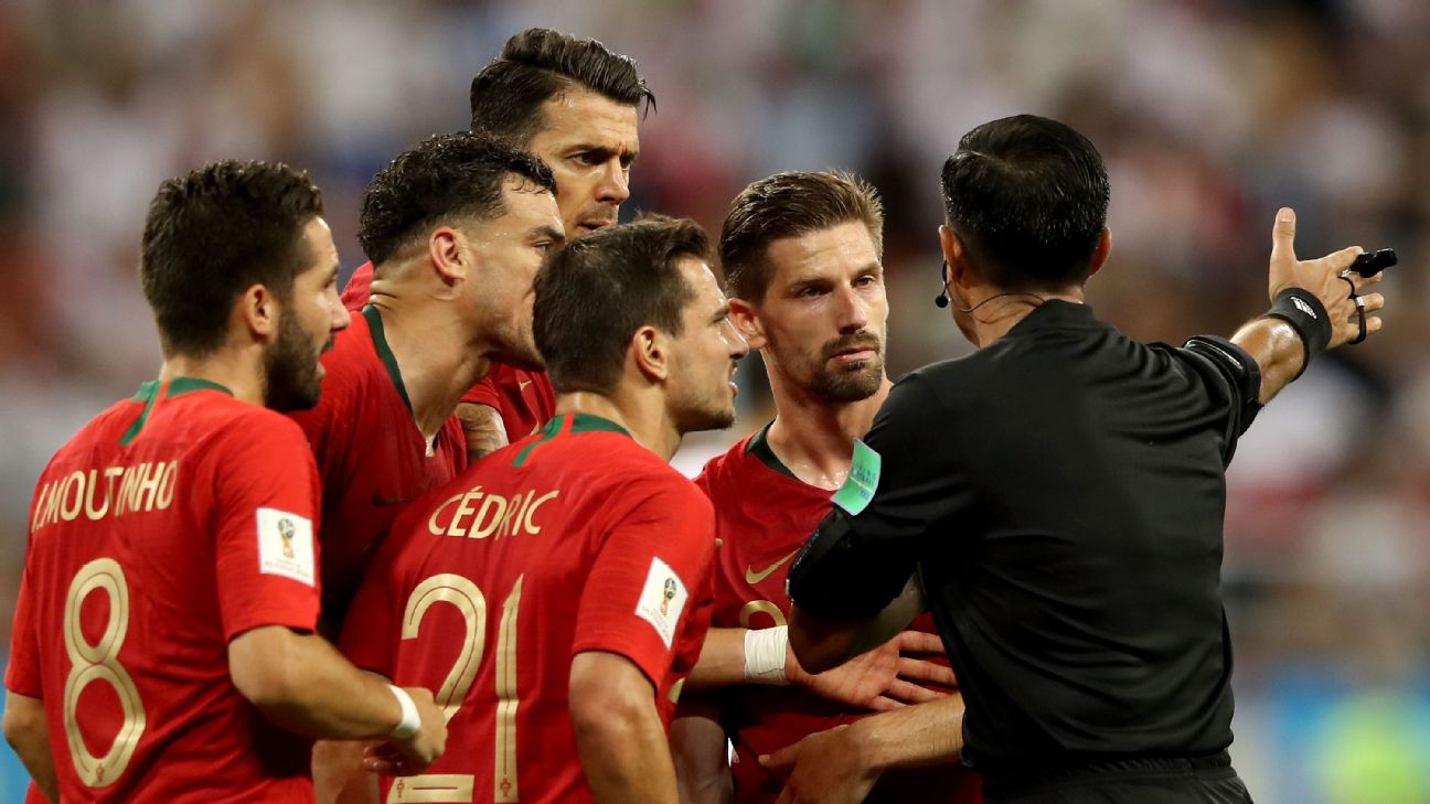 Portugal players surround the referee during their World Cup group-stage match against Iran.