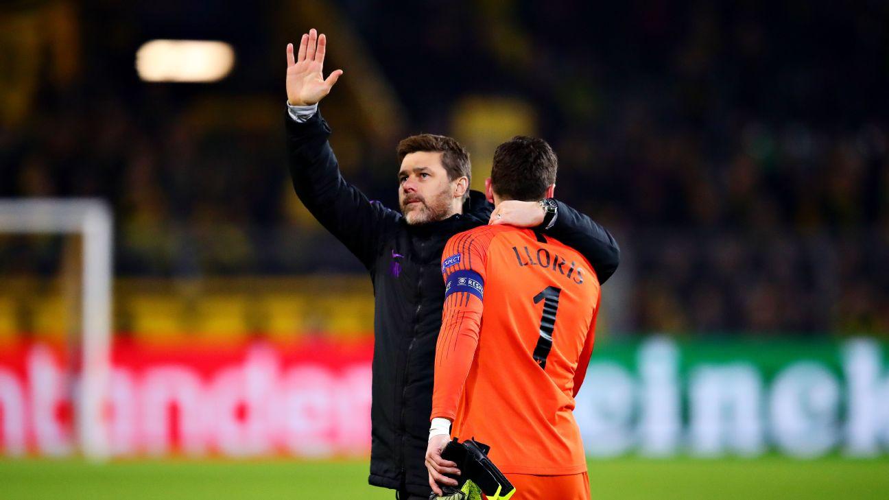 Mauricio Pochettino, arm raised, celebrates with Hugo Lloris after Tottenham's win against Borussia Dortmund.