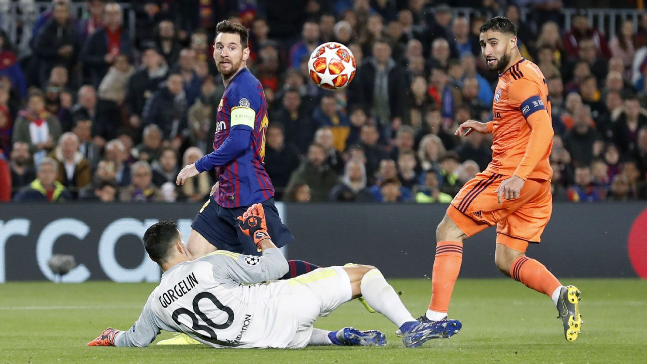Lionel Messi chips the ball over Lyon's goalkeeper during their Champions League match.