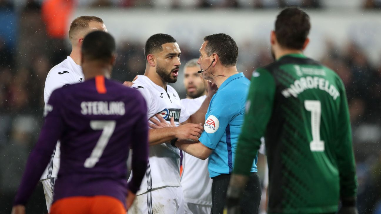 Swansea City players argue with the referee after he awarded Manchester City a penalty in their FA Cup match.