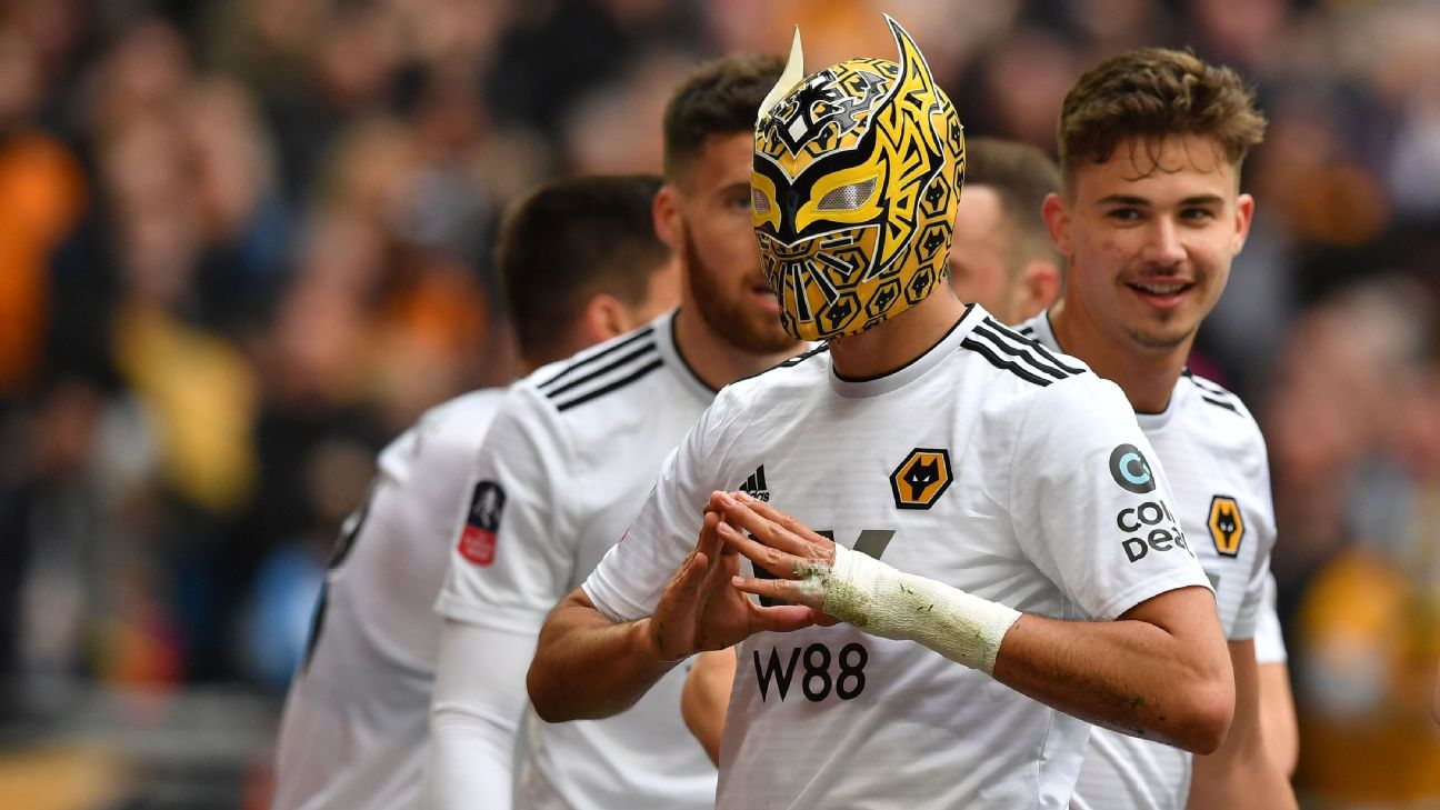 Wolverhampton Wanderers' Mexican striker Raul Jimenez wears a mask as he celebrates scoring his team's second goal during the  FA Cup semifinal football match against Watford.