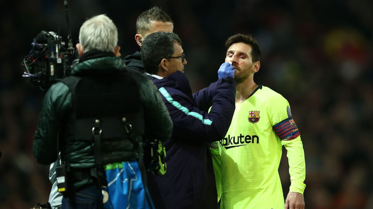 Barcelona medical staff tend to Lionel Messi after he was hit in the face against Manchester United.