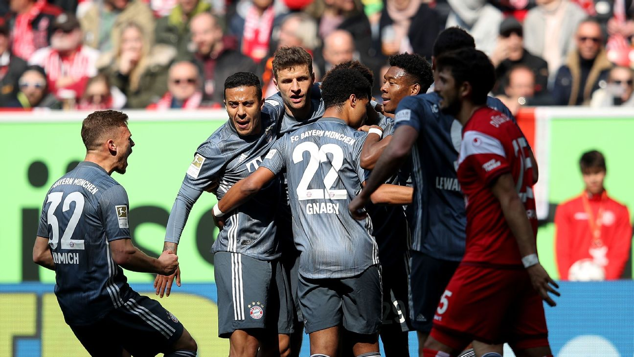 Bayern Munich's forward Thomas Mueller (3rdL) is congratulated by teammates after scoring his team's opening goal