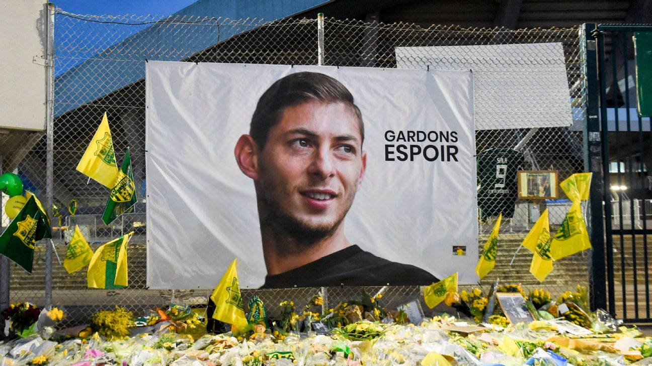 Flowers, messages and candles are placed in front of a giant portrait of Emilianio Sala