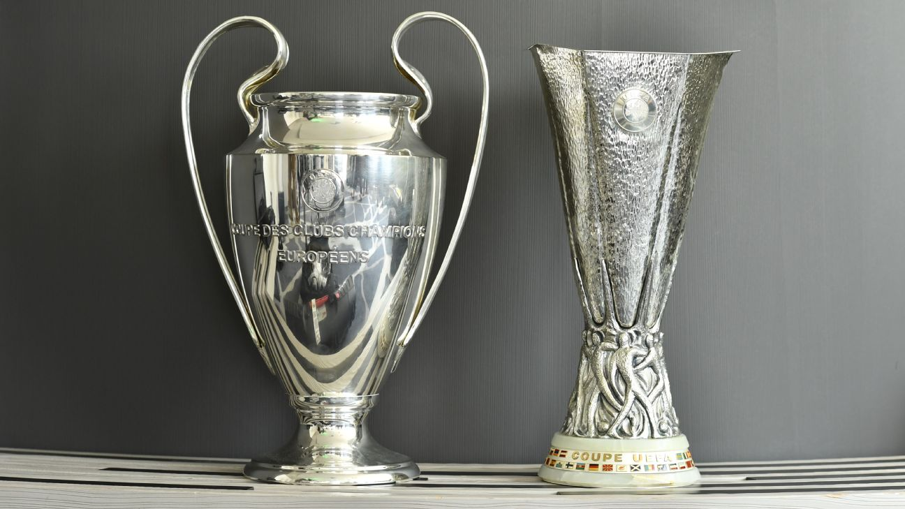 The UEFA Champions League and Europa Legue trophies are displayed.