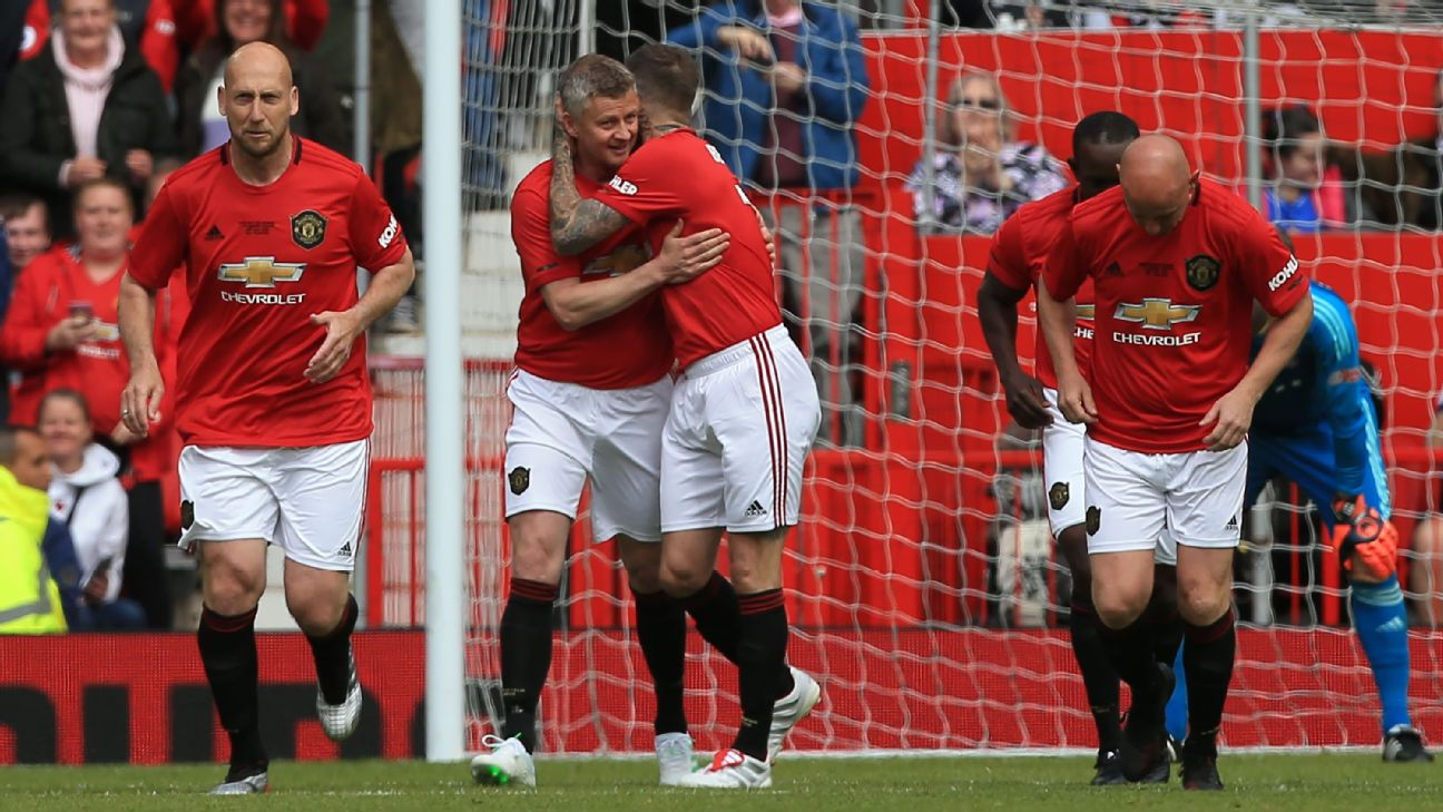 Ole Gunnar Solskjaer celebrates with David Beckham after scoring in Manchester United's legends match against Bayern Munich.