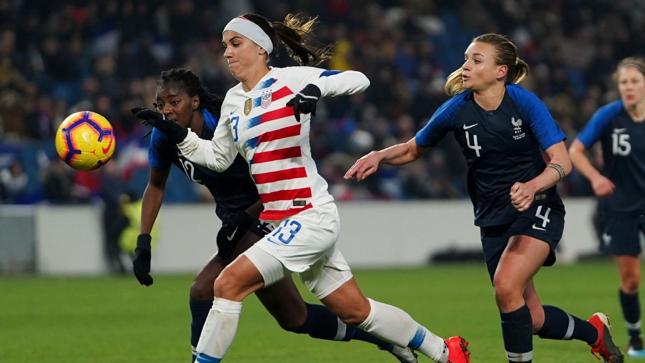 Alex Morgan battles against defenders during the U.S.'s friendly against France.