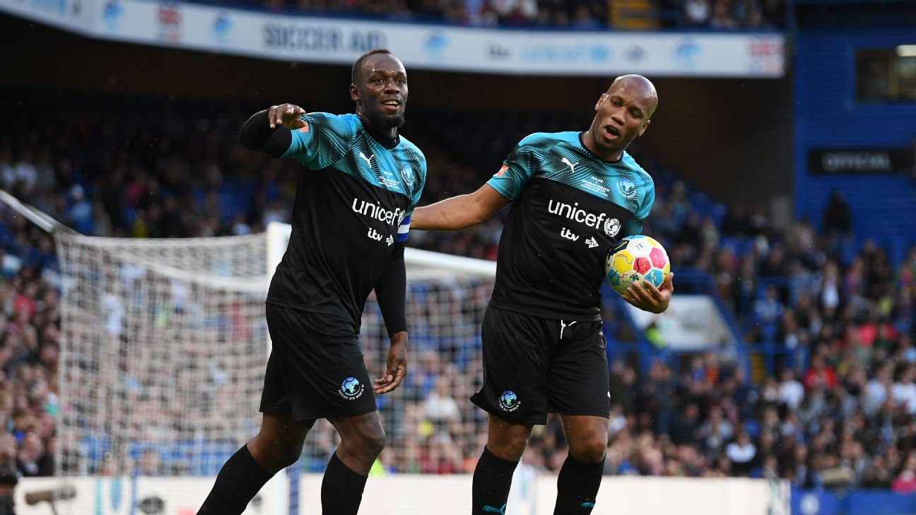 Usain Bolt, left, celebrates with Didier Drogba after scoring a goal in the Soccer Aid for UNICEF charity match at Stamford Bridge.