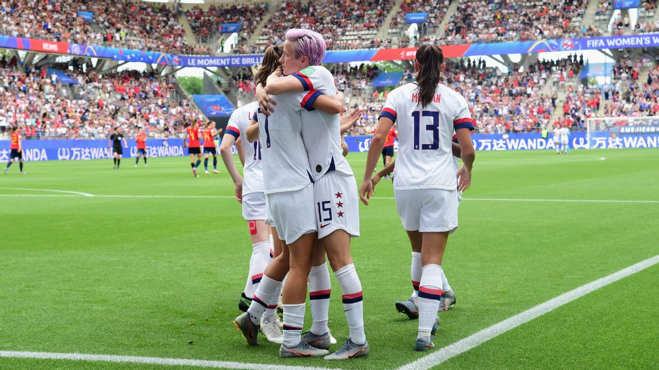 United States women's team players celebrate after scoring a goal against Spain in the World Cup.