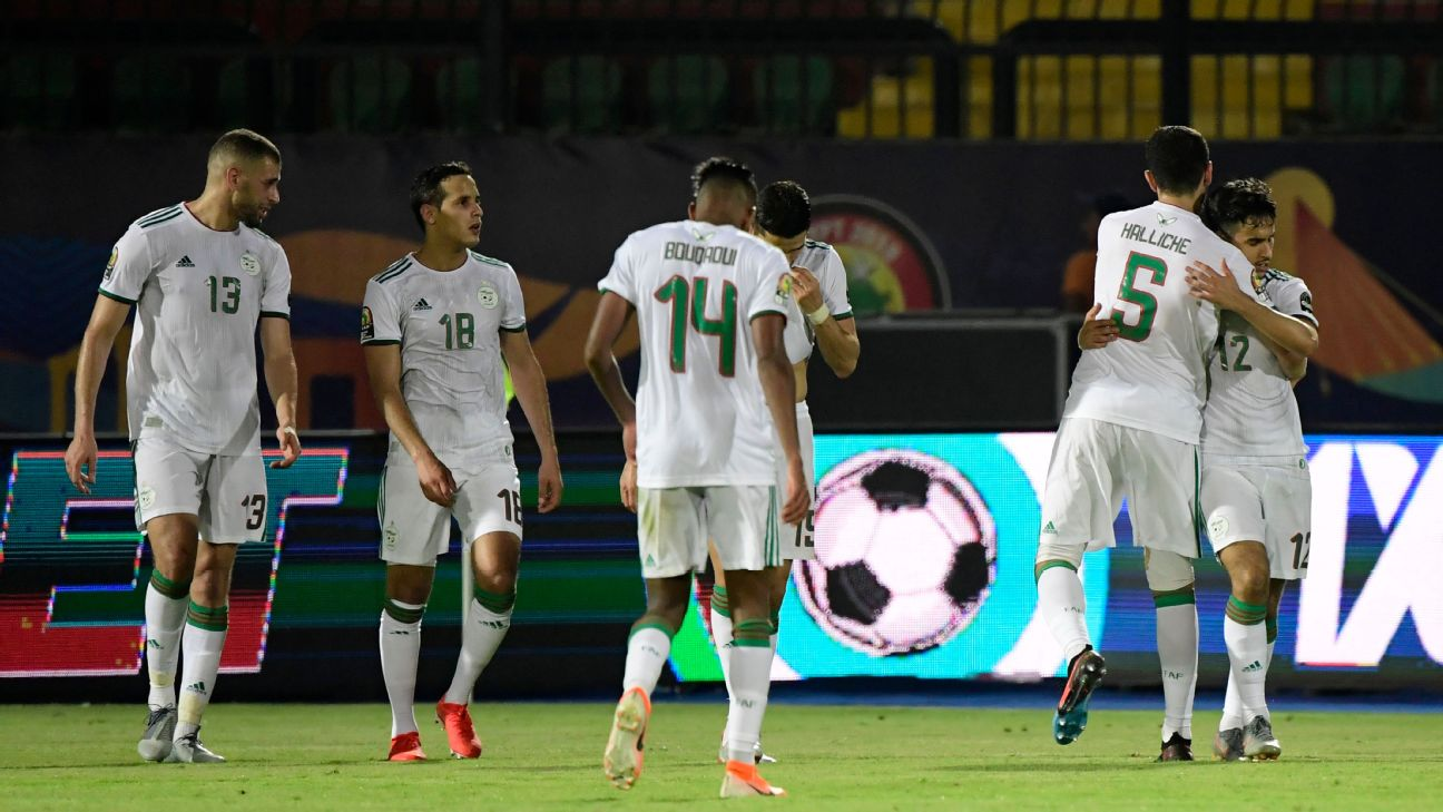 Algeria's forward Adam Ounas, right, celebrates after scoring a goal against Tanzania.