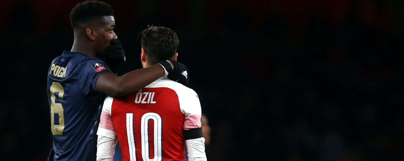 Paul Pogba of Manchester United and Mesut Ozil of Arsenal talk together