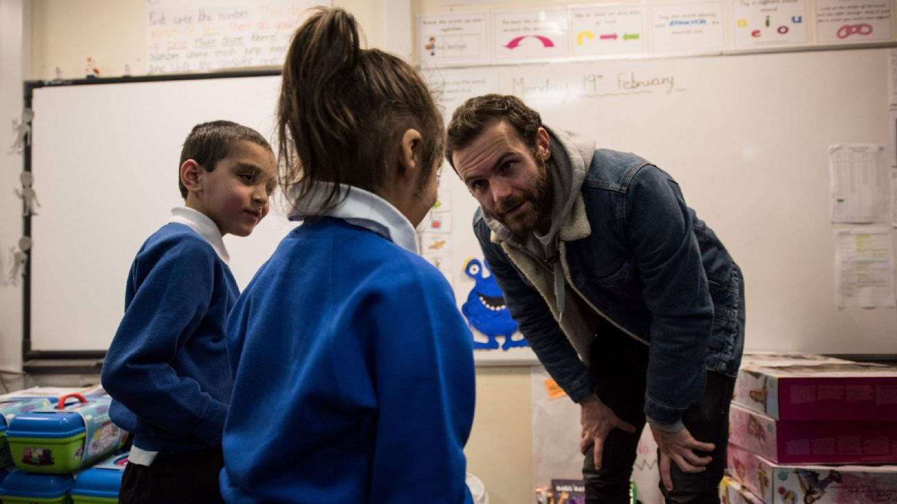 Manchester United's Spanish midfield player Juan Mata presents gifts to pupils