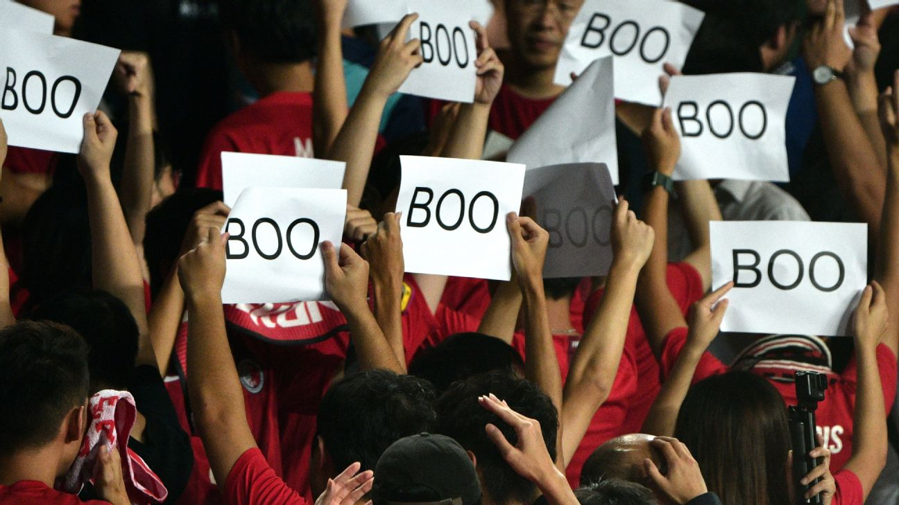 Hong Kong fans turn their back and boo while holding up placards during the Chinese anthem