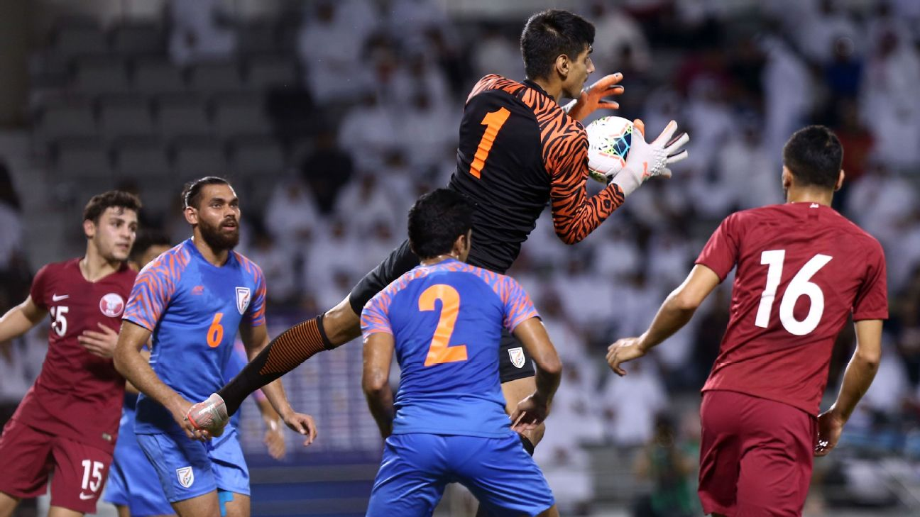 India's goalkeeper Gurpreet Singh Sandhu (in black) rises to catch a ball, while defenders Adil Khan (left) and Rahul Bheke (centre) look on, during India's World Cup qualifier against Qatar in Doha.