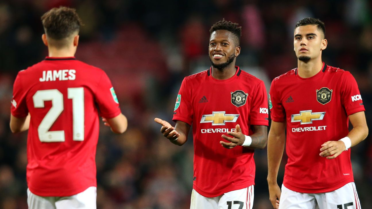 Daniel James celebrates with Manchester United teammates after hitting a penalty in a shootout.