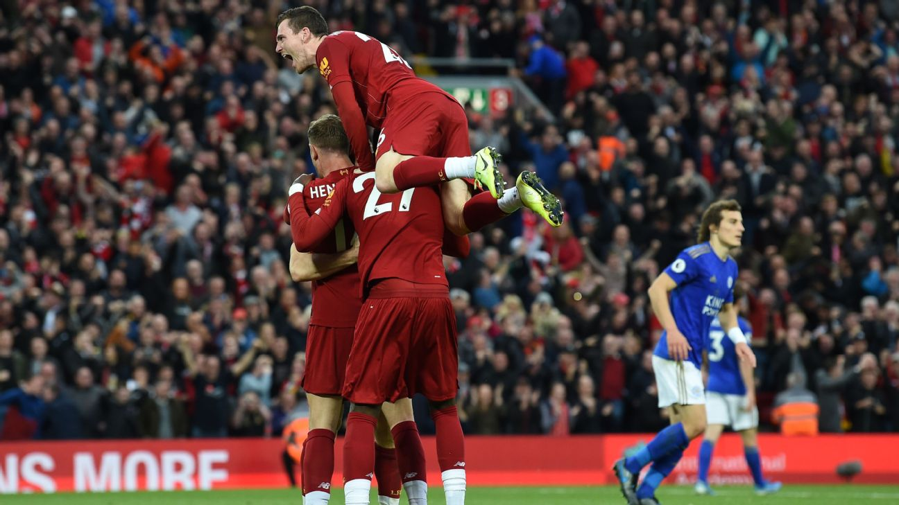 Liverpool's English midfielder James Milner celebrates with teammates after taking a penalty