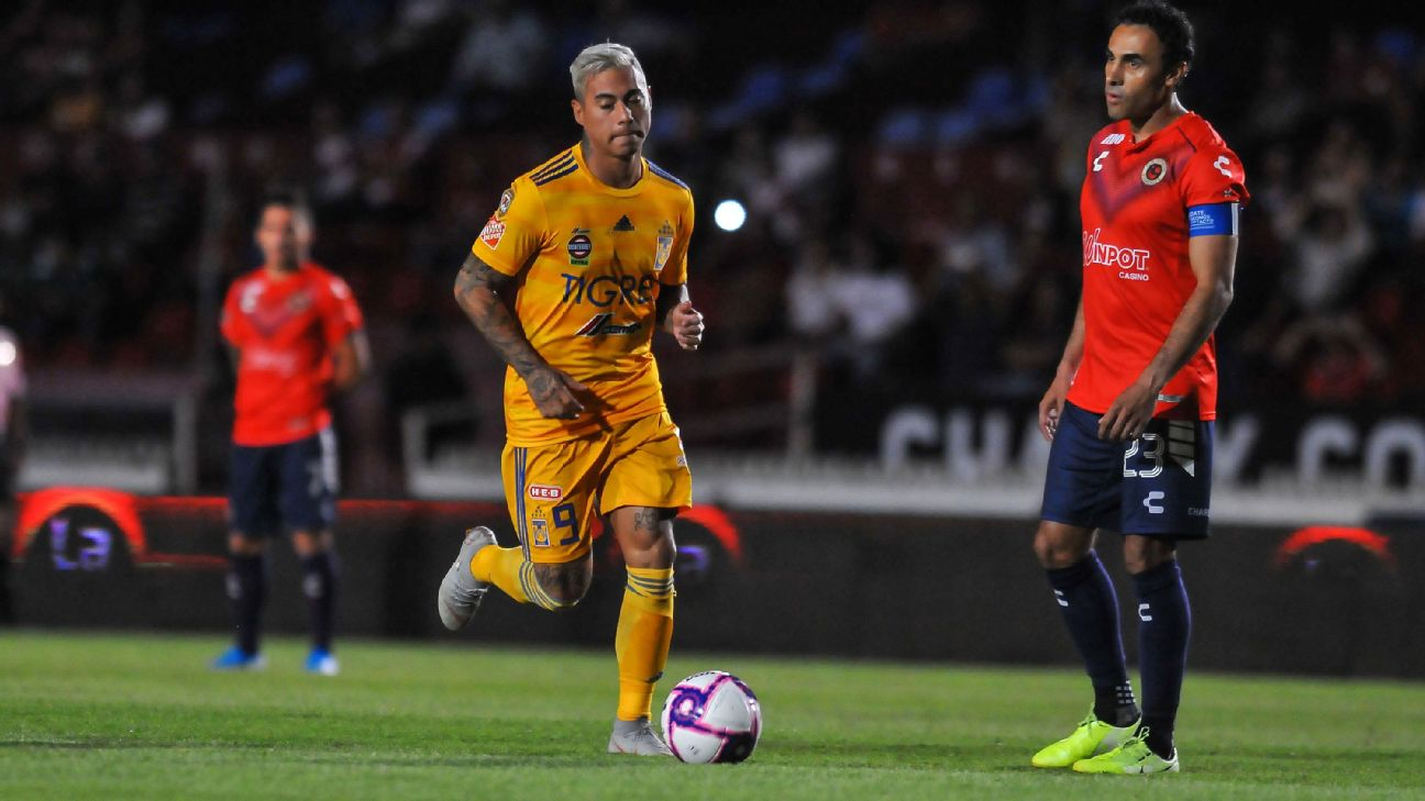 Veracruz players, in red, stand in protest as Tigres player Eduardo Vargas dribbles the ball in a Liga MX match.