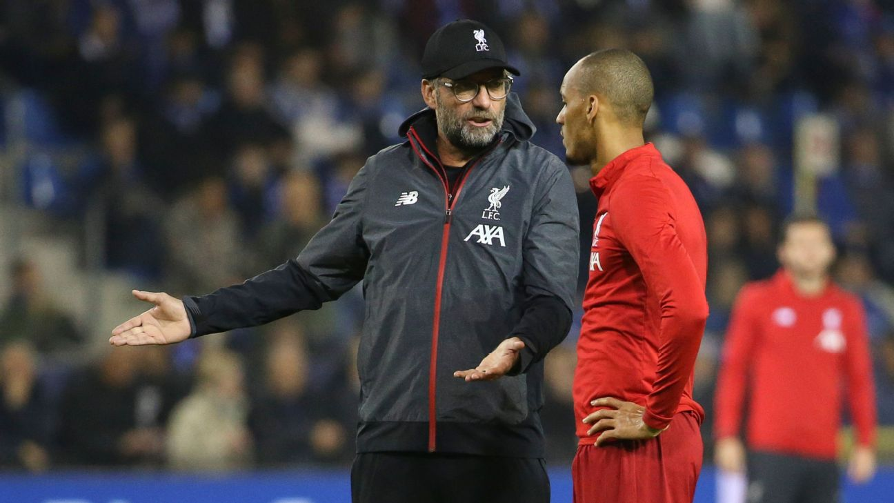 Liverpool manager Jurgen Klopp, left, speaks with Fabinho during their Champions League match against Genk.