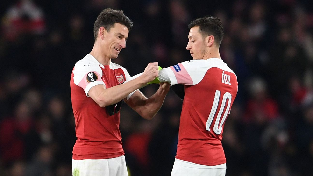 Laurent Koscielny hands the captains armband to Mesut Ozil