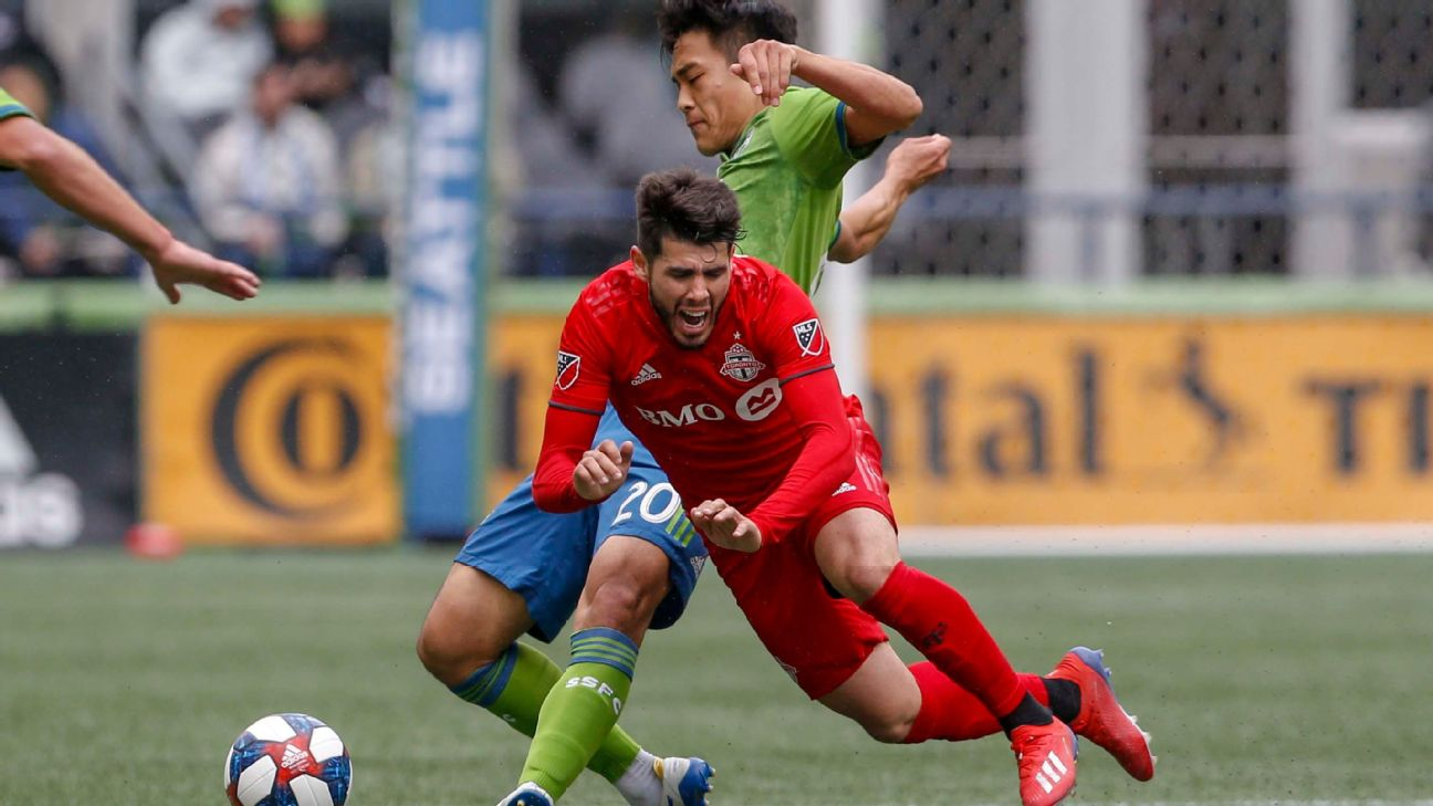 Kim Kee-hee and Alejandro Pozuelo challenge for the ball during the MLS match between the Seattle Sounders and Toronto FC.