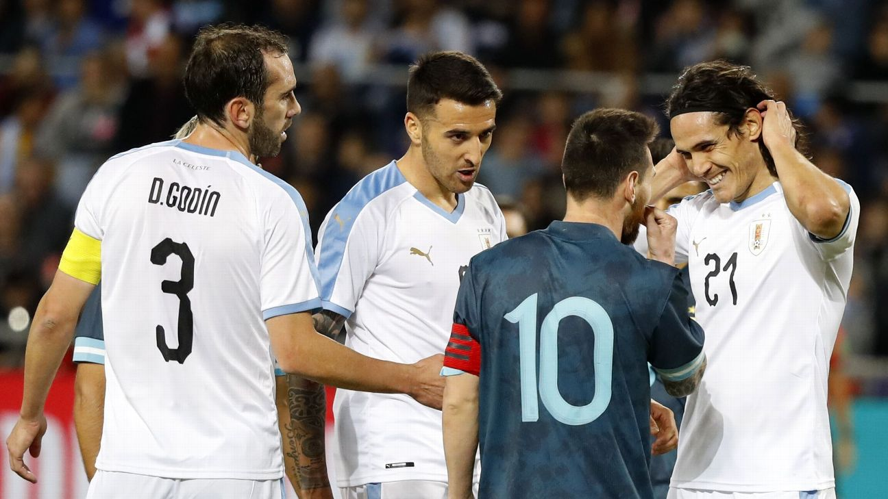 Argentina's forward Lionel Messi talks to Uruguay's forward Edinson Cavani