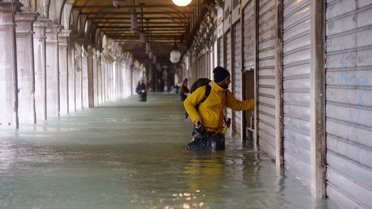 A man stands near a closed shop in St. Mark's Square during the flooding in Venice.