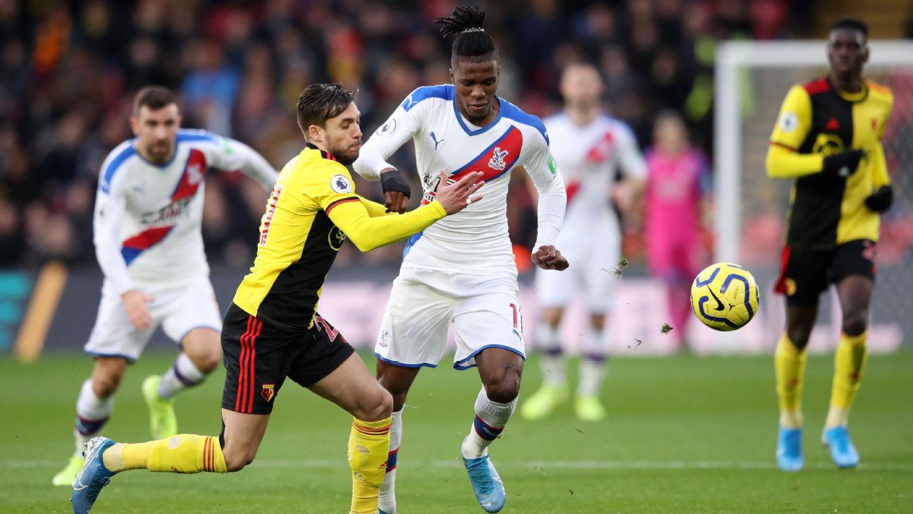 Wilfried Zaha of Crystal Palace is challenged by Kiko Femenia of Watford