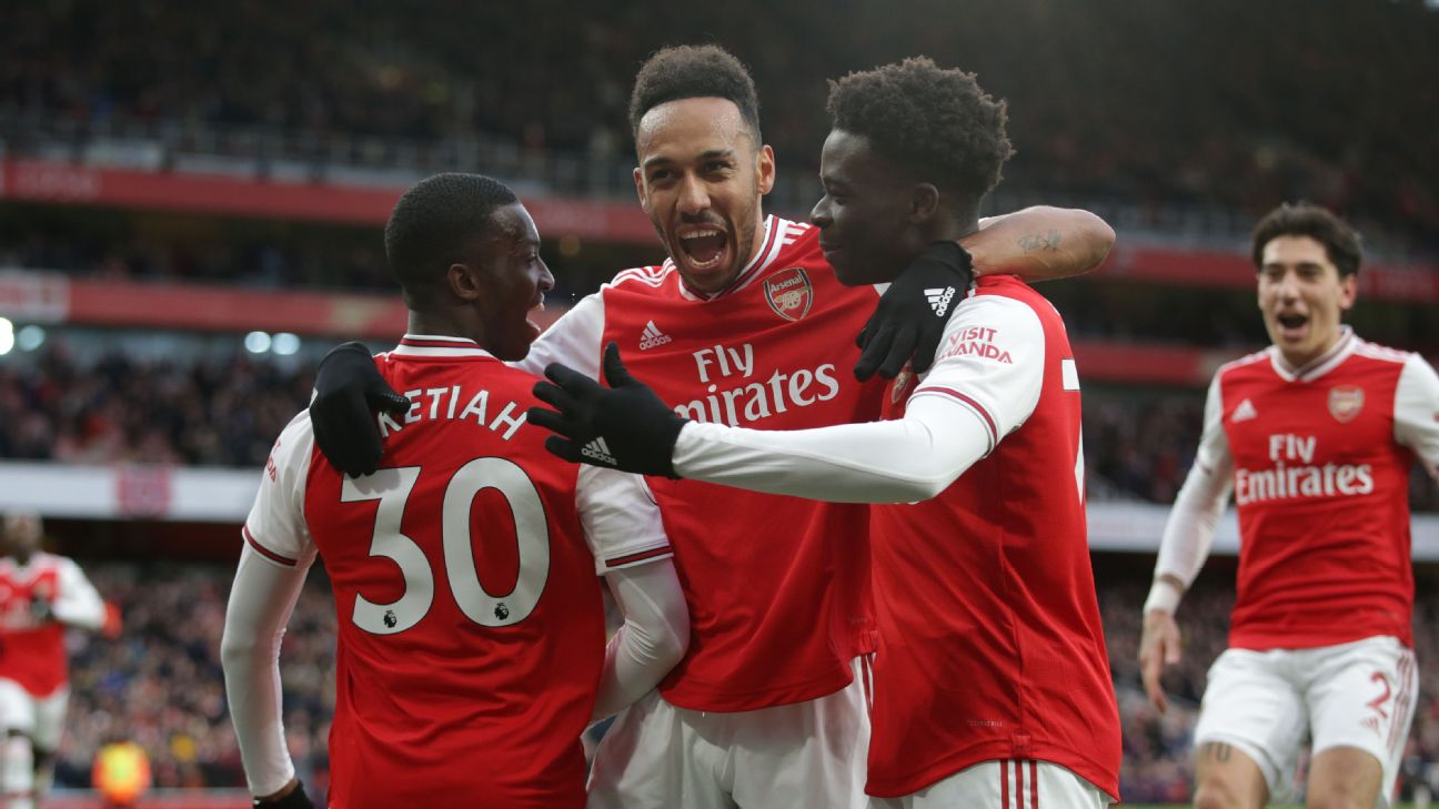Arsenal players celebrate after scoring a goal against Everton in the Premier League.